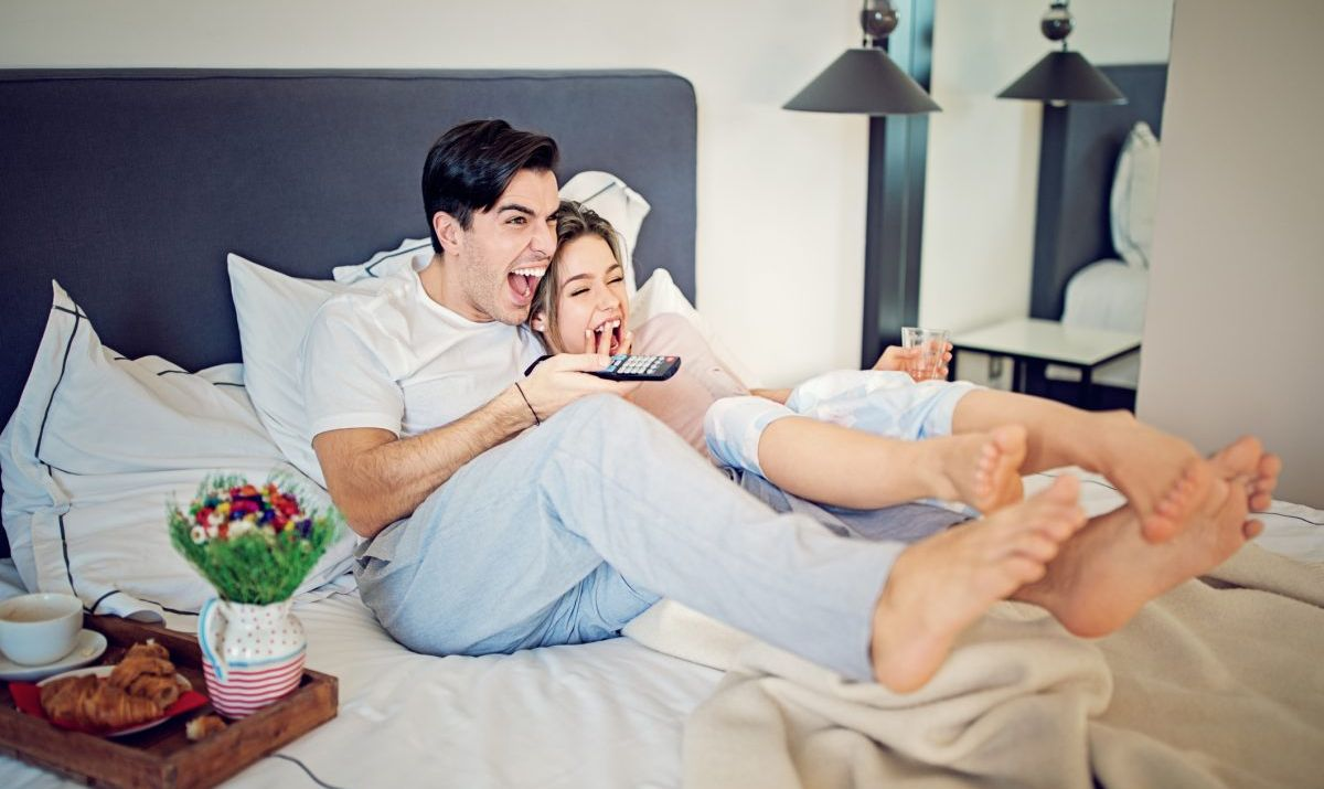 Couple is watching comedy film on TV in the bed