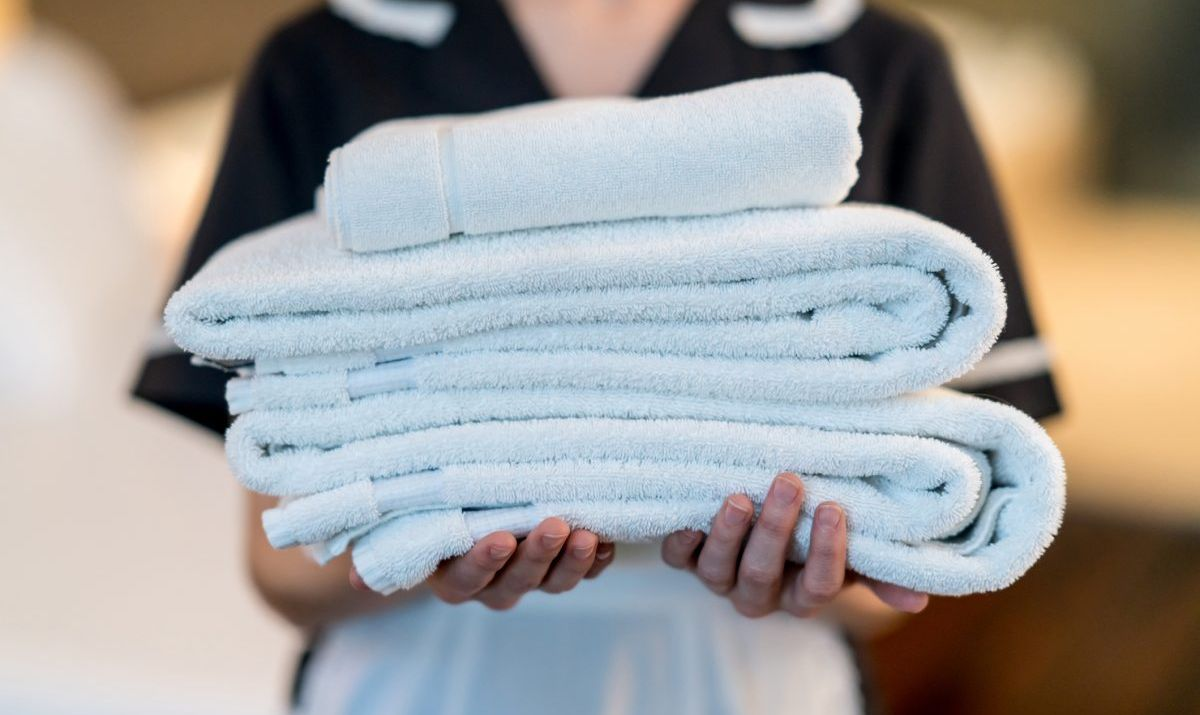 Unrecognizable housekeeper holding towels at a hotel