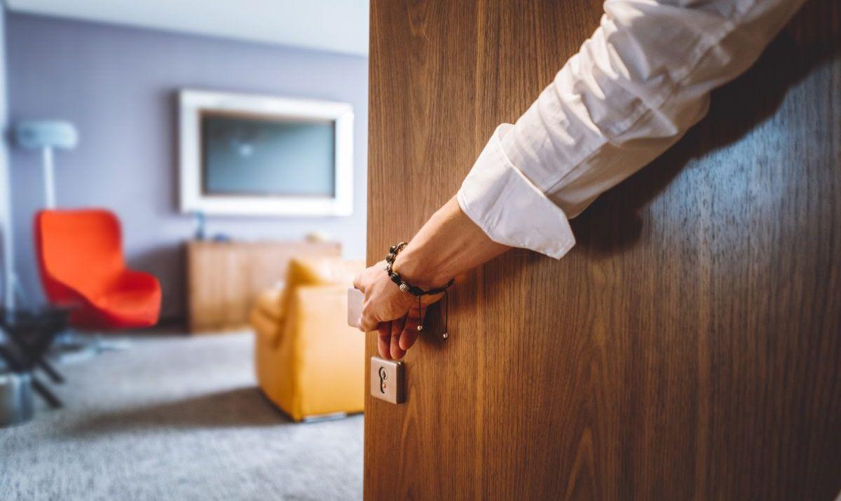 Man hand opening the door of the luxurious hotel room