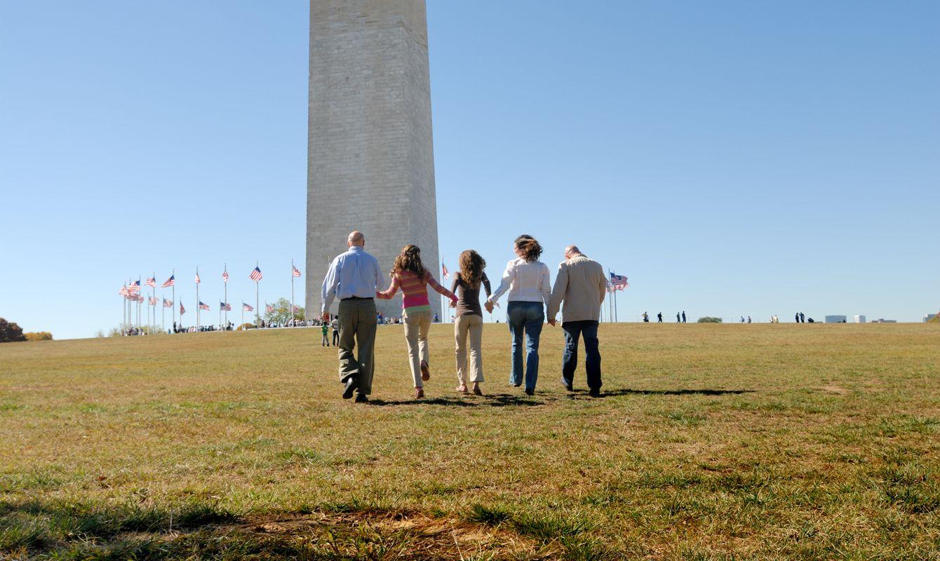 """Multi-generational family of five walk up hill toward the Washington Monument in Washington, D.C. Copyspace."""