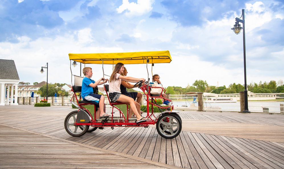 Young happy family riding a double surrey tandem bicycle on a large ocean boardwalk. Outdoor summer fun with kids