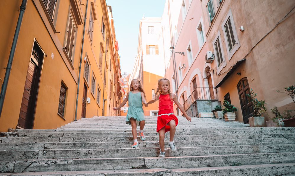 Adorable little girls on vacation in Italy running and having fun outdoors