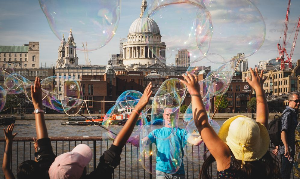 Young kids having fun with soap bubbles made by a street performer on the South Bank of the Thames