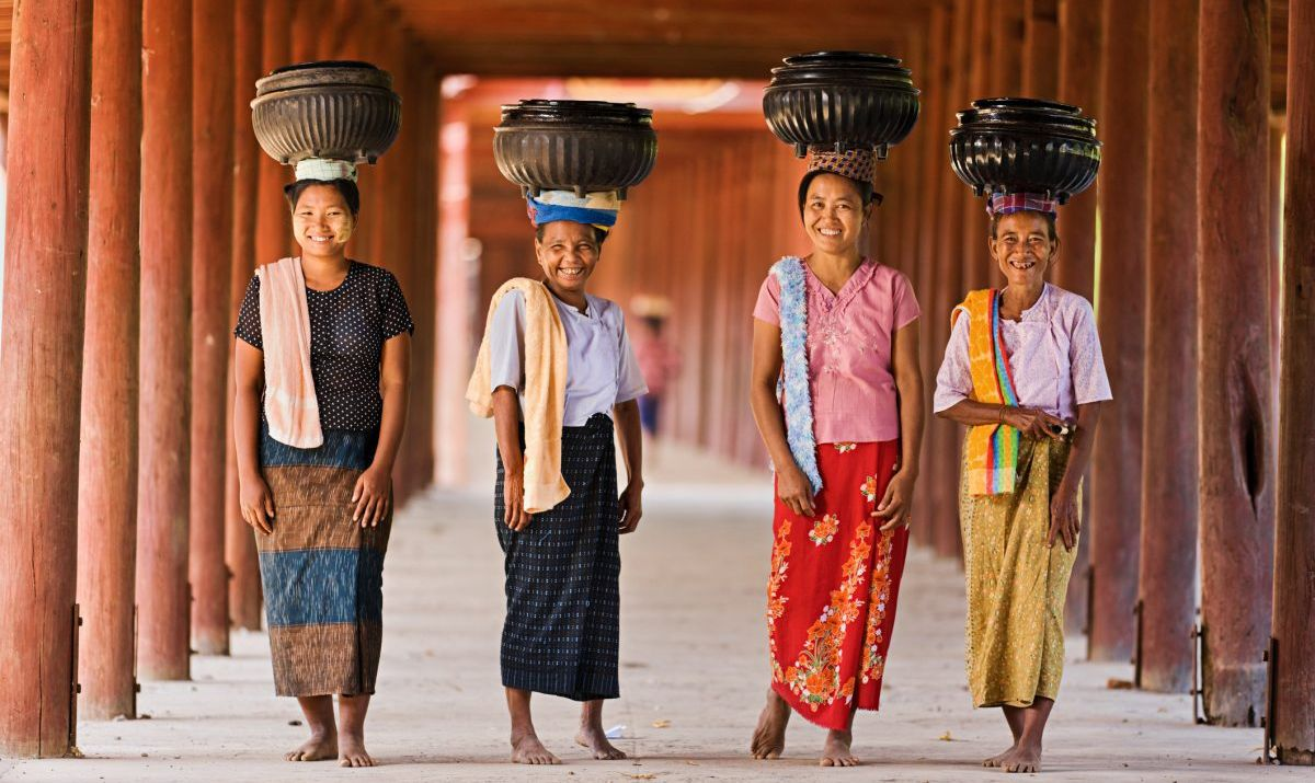 Burmese women posing for a picture as they carry rice to the monastery