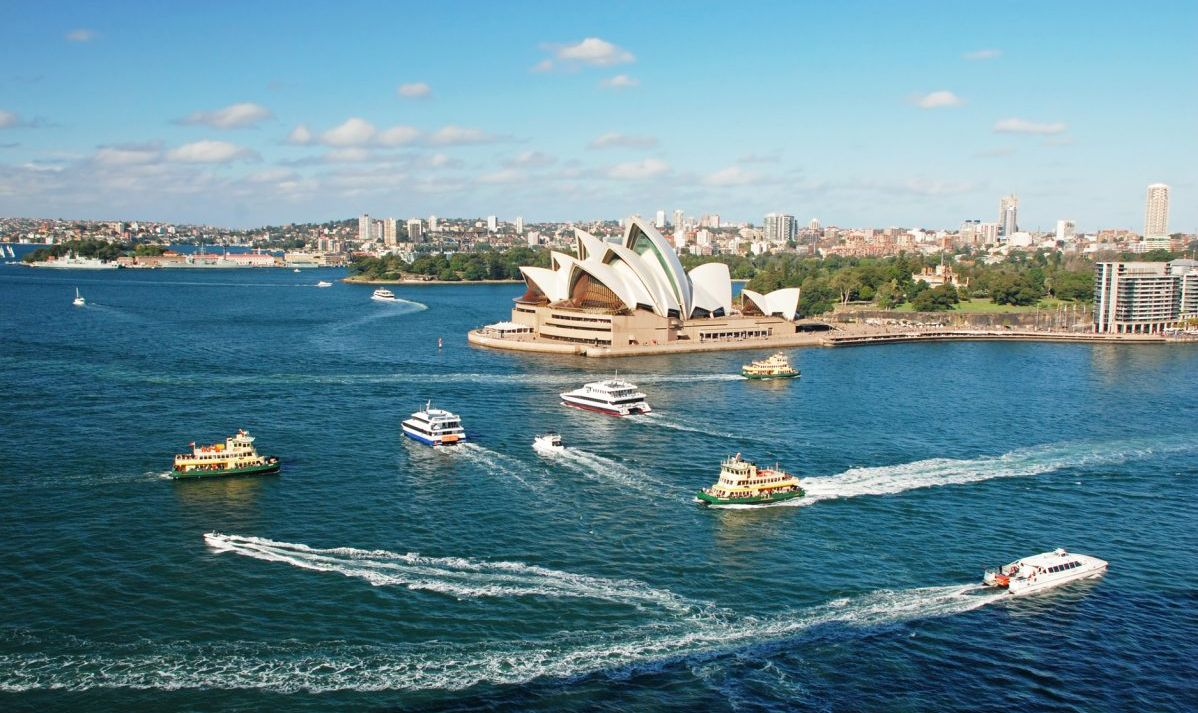 Boats steaming left and right past the Sydney Opera House