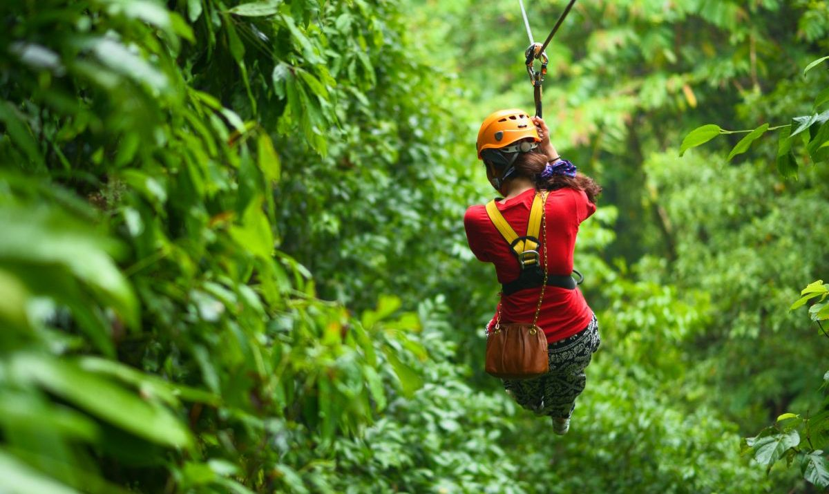 Traveler ziplining through a rainforest in southeast Asia.