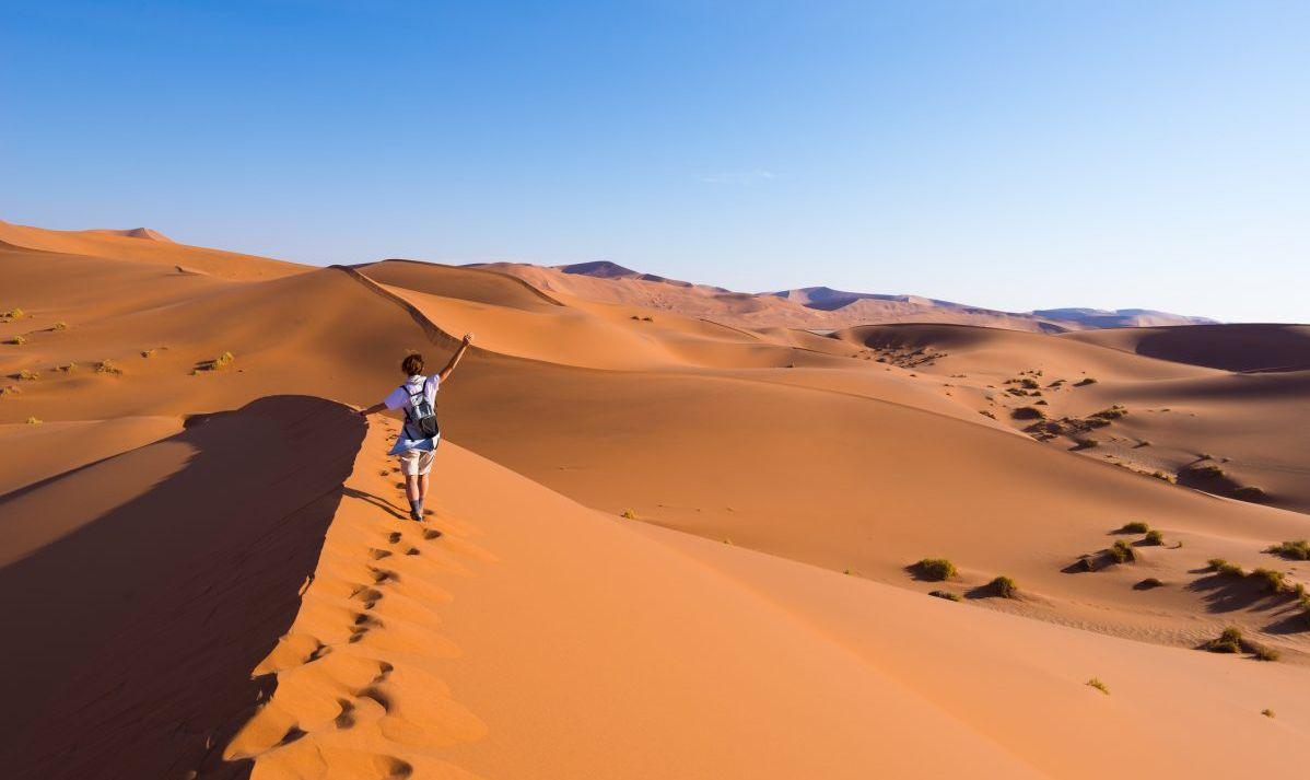 Woman walking on sand dunes of Sossusvlei in Namibia.