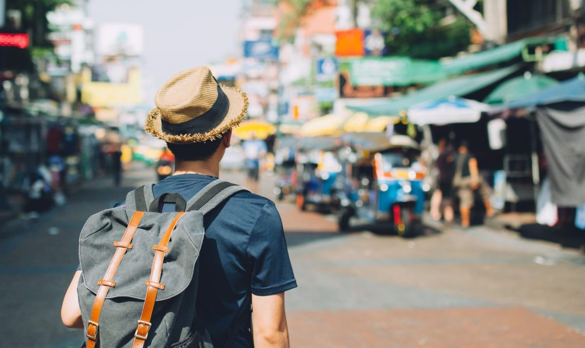 Traveler among locals and shops in southeast Asia.