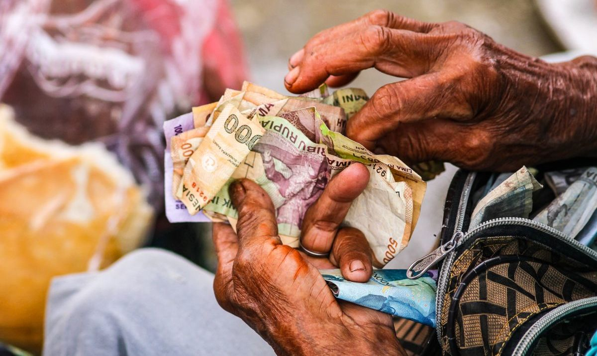 Elder counting Rupiah in Indonesia.