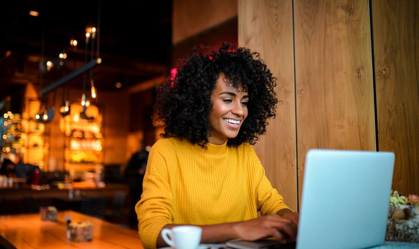 Smiling woman using laptop at the bar.