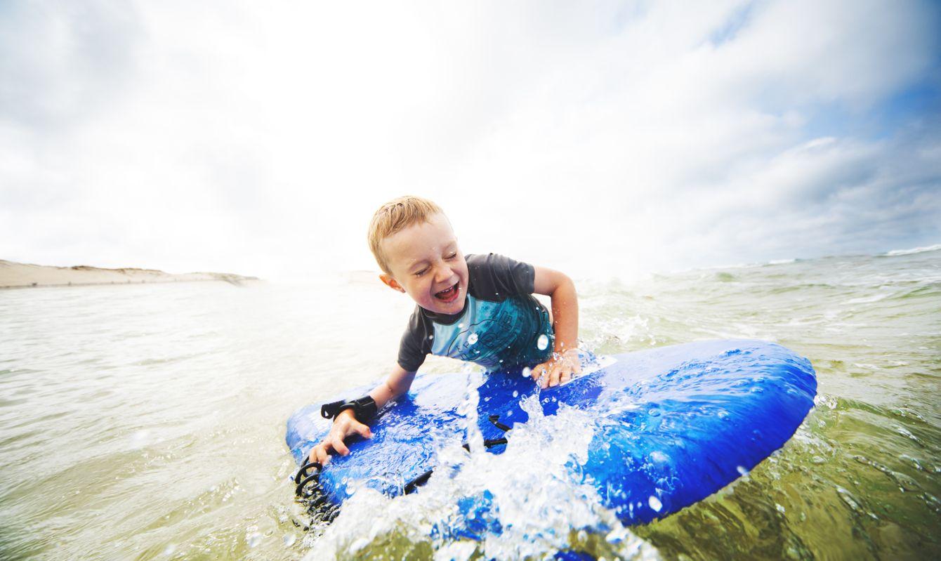Little boy bodyboarding at the sea