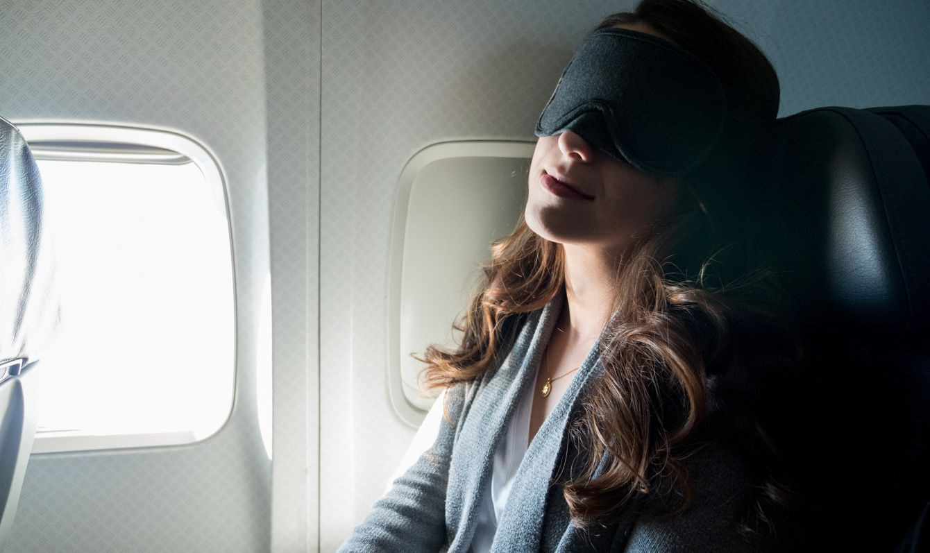 With her mask on to help her sleep, the woman gets good, deep sleep during her flight.