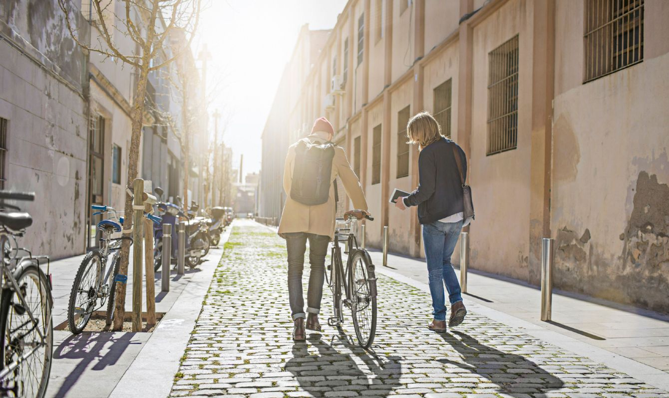 Man with bicycle and friend in city on sunny day