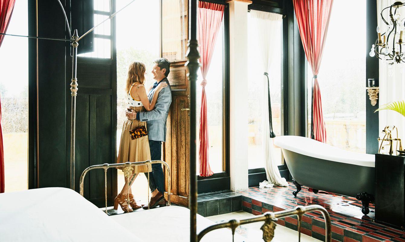 Embracing couple standing in doorway of room in boutique hotel