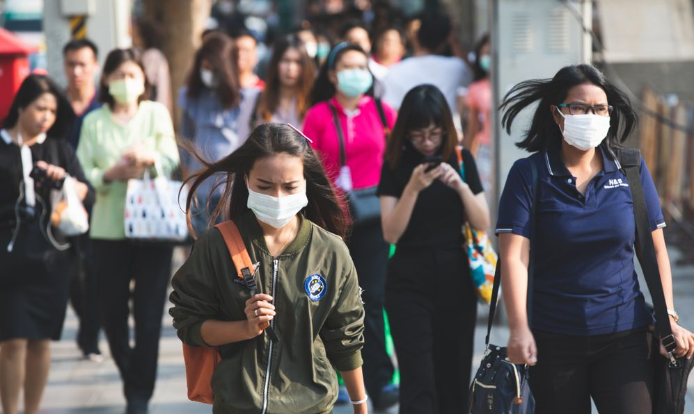 Unidentified people wearing mouth mask against air smog pollution