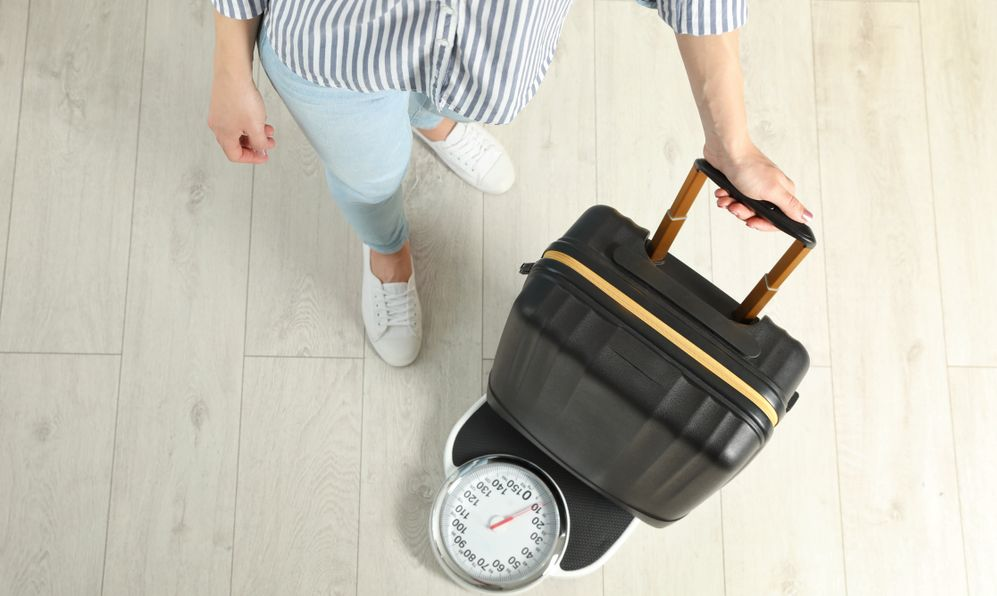 Woman weighing suitcase indoors, top view