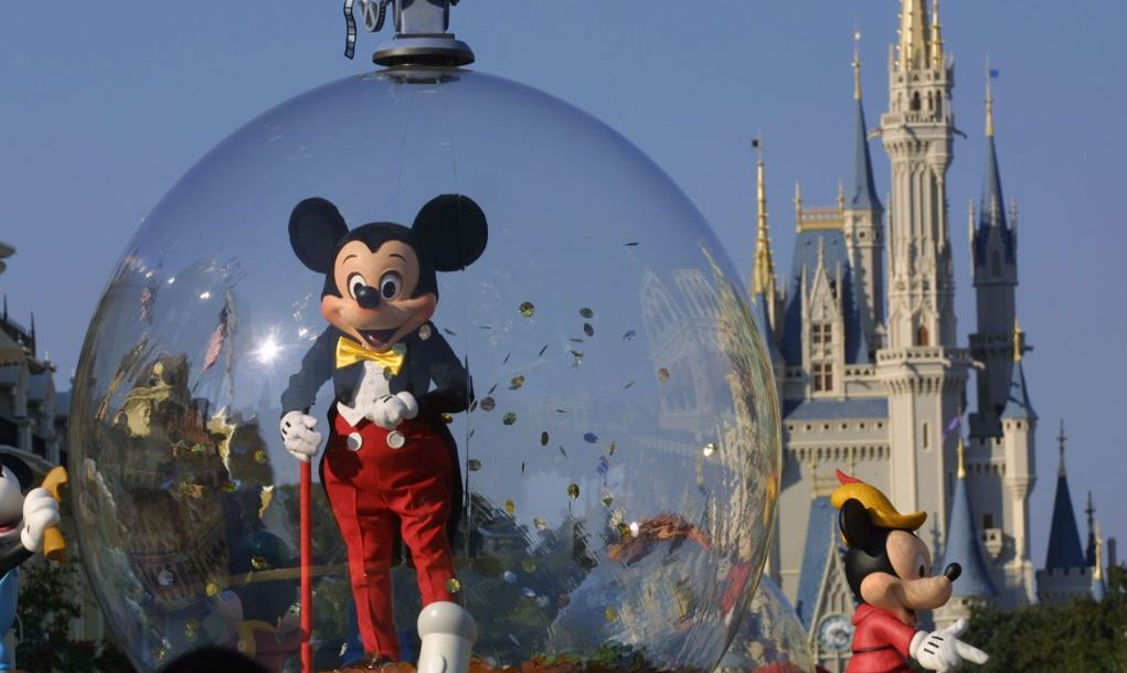 Mickey Mouse in front of Cinderella's castle at Disney World's Magic Kingdom.
