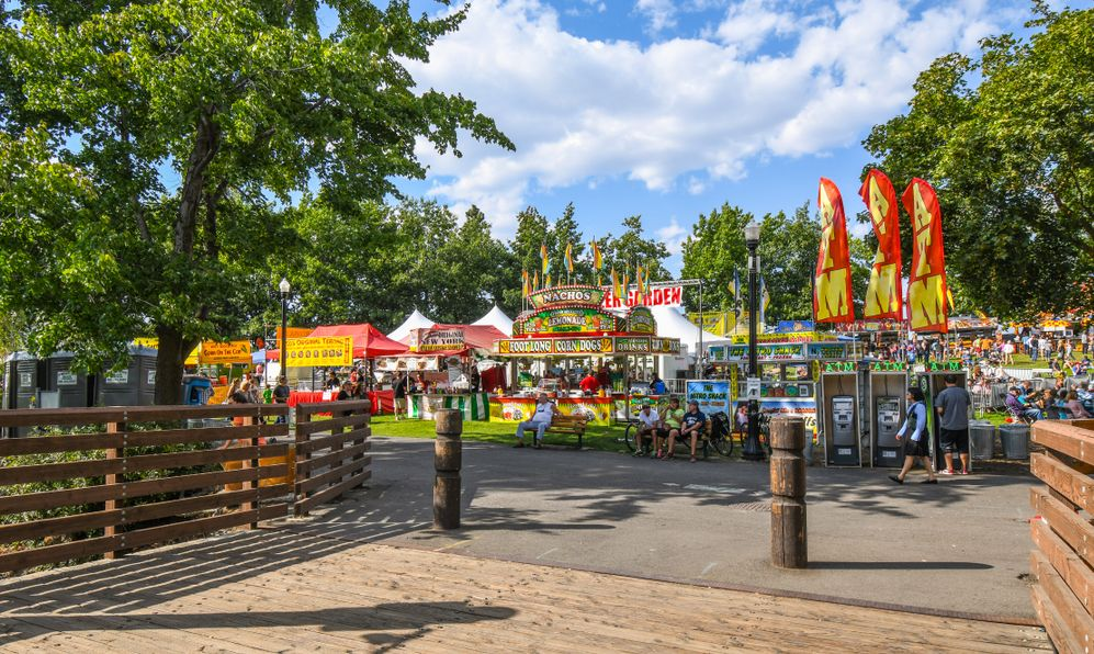 Visitors enjoy the food booths and vendors on the first day of Pig Out In the Park, in Riverfront Park, Spokane, Washington