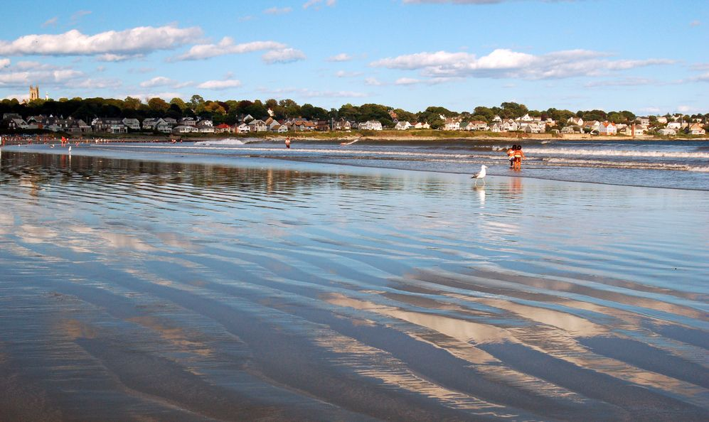 The sky is reflected in the shallow, rippled waters of a Easton Beach in Newport, Rhode Island