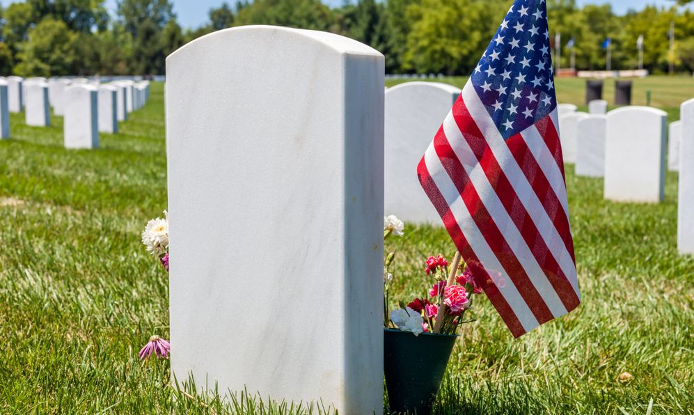 The United States National flag with white headstones in the background in Camp Butler National cemetery