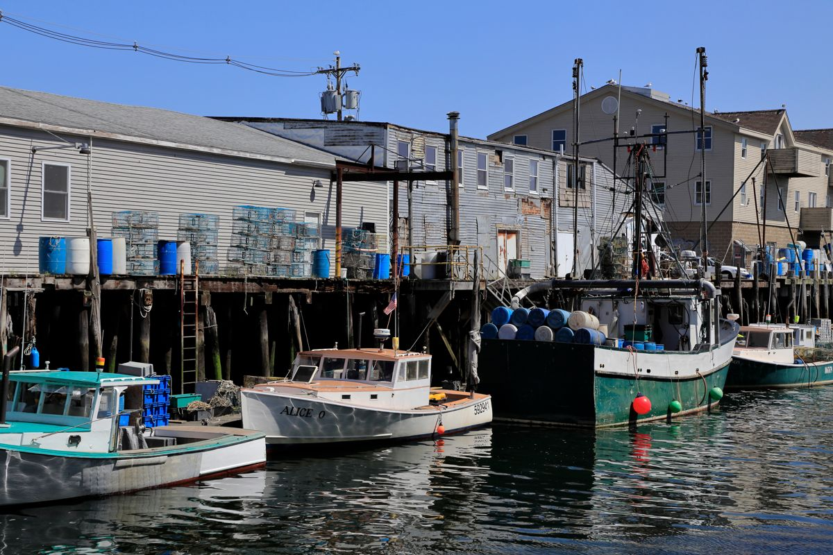 Portland.Maine. USA Fishing boats and lobster boats docking in Old Port with old warehouse on the dock in the background