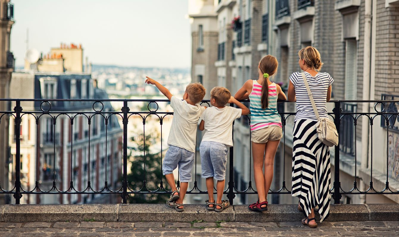 Mother and kids visiting Paris. They are watiching beautiful Paris view from the top of Montmartre. One of the boys is pointing at something.