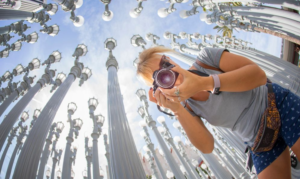 A cheerful funny tourist girl taking photos with a camera at the famous artwork Urban Lights by Chris Burden at LACMA
