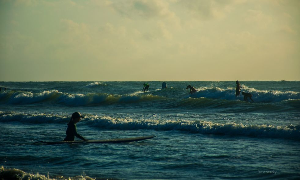 People Surfing at Padre Island Texas on the Gulf Coast on a summer morning on April 30 2014