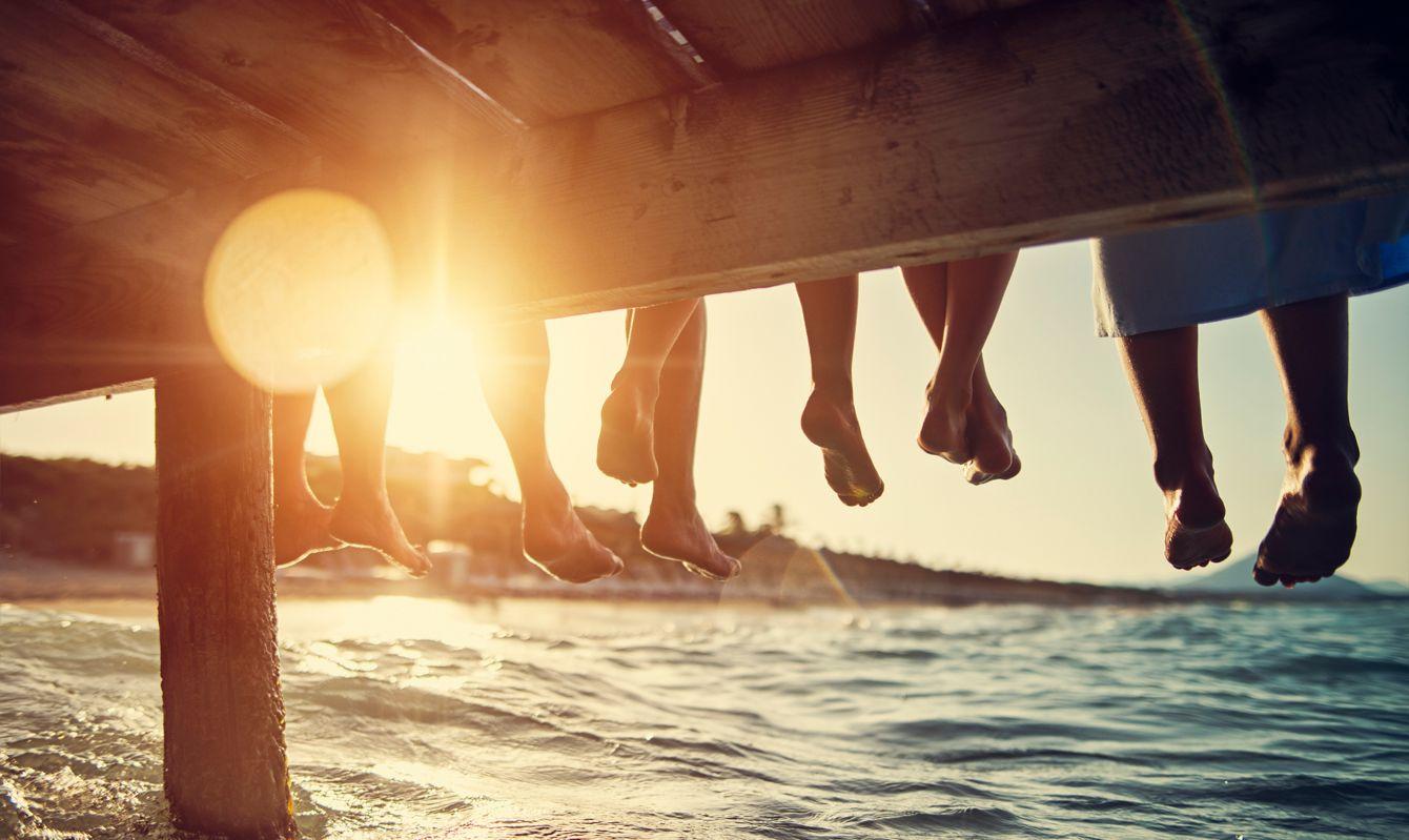 Five people having fun sitting on pier. Feet shot from below the pier. Sunny summer day evening. Nikon D850