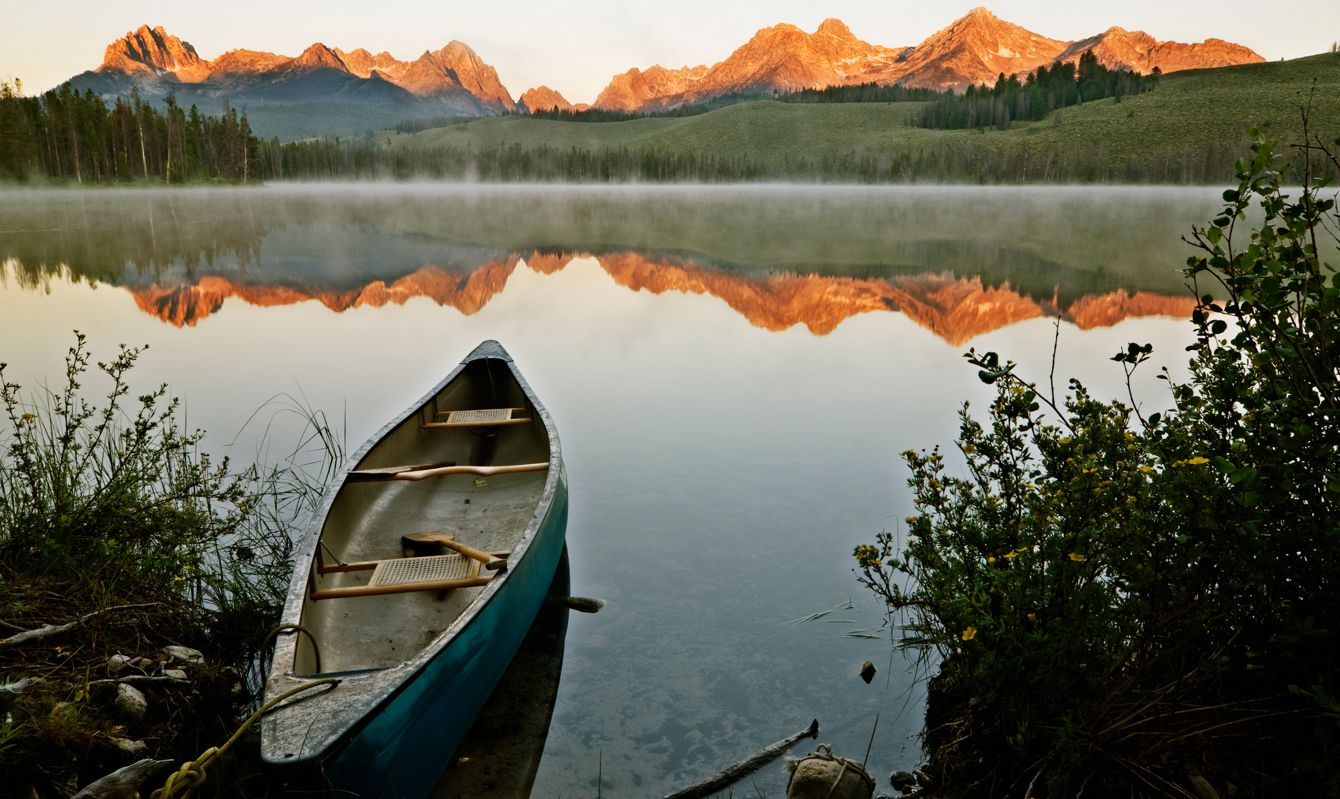 Beautiful first light hitting Sawtooth mountain range as seen from Little Redfish Lake, Stanley, Idaho, USA with a kayak ready to go
