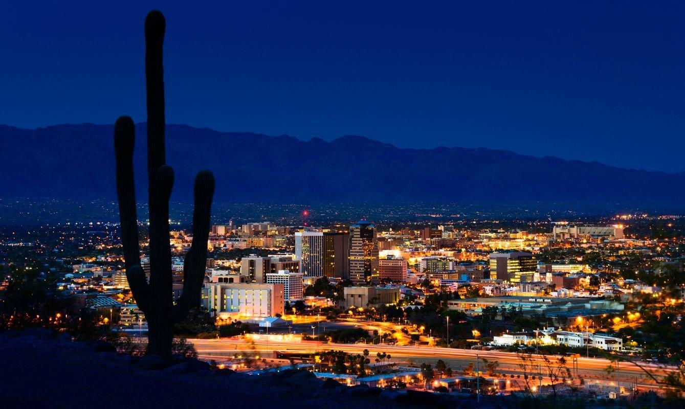 Tucson Arizona at night framed by saguaro cactus and Santa Catalina Mountains