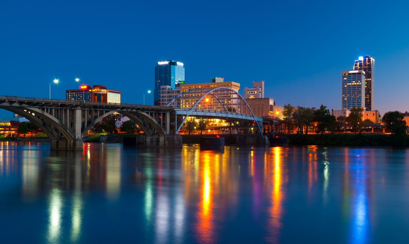 Little Rock downtown skyline with a bridge and the Arkansas River in the foreground at dusk.