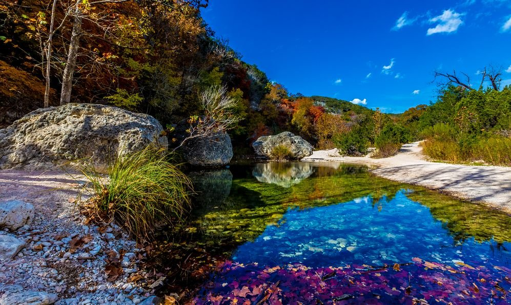 Crystal Clear Pool on the Sabinal River with Beautiful Fall Foliage and Large Boulders at Lost Maples State Park, Texas