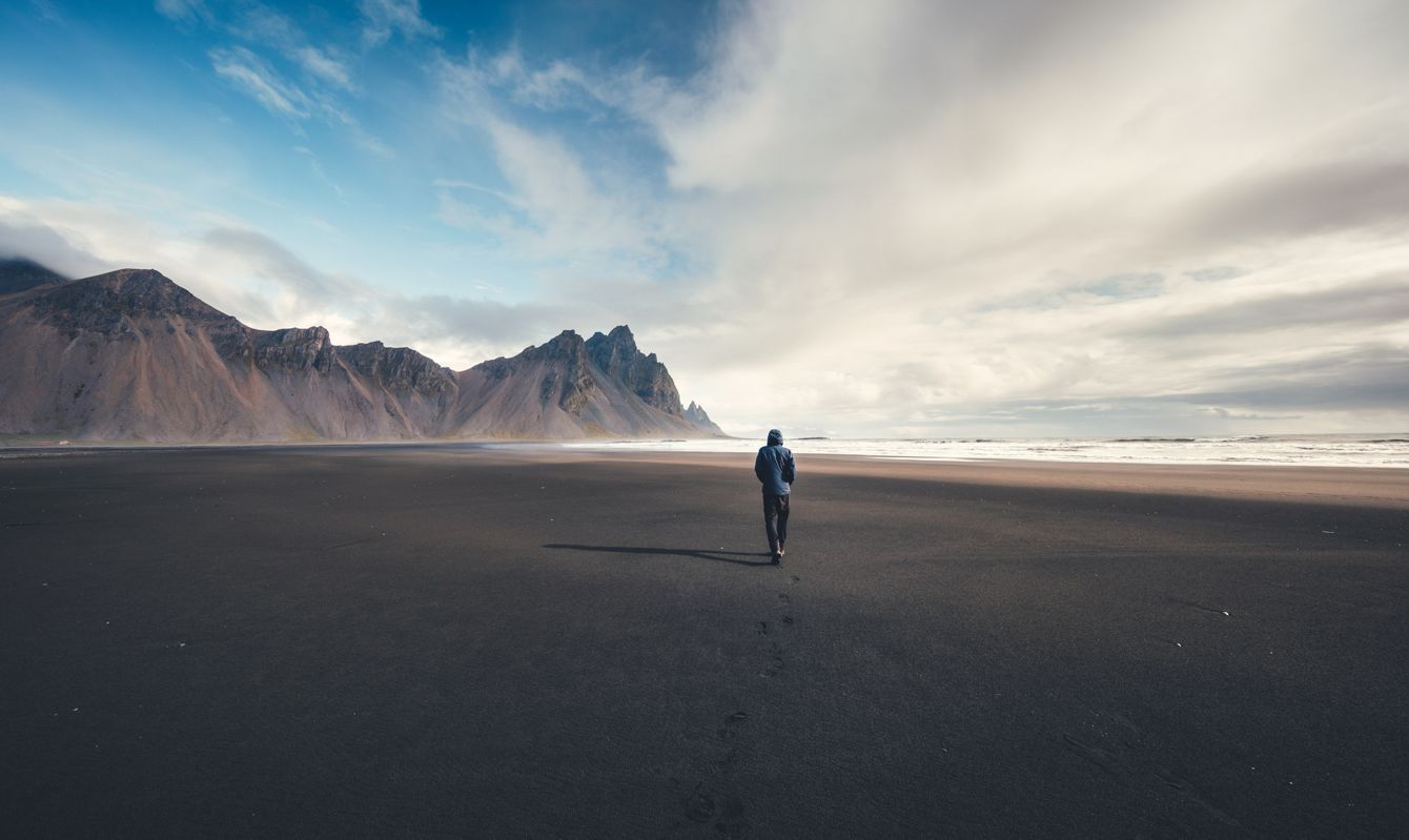 Man walking on black beach towards Vestrahorn mountain (Stokksnes peninsula in Southeast Iceland).