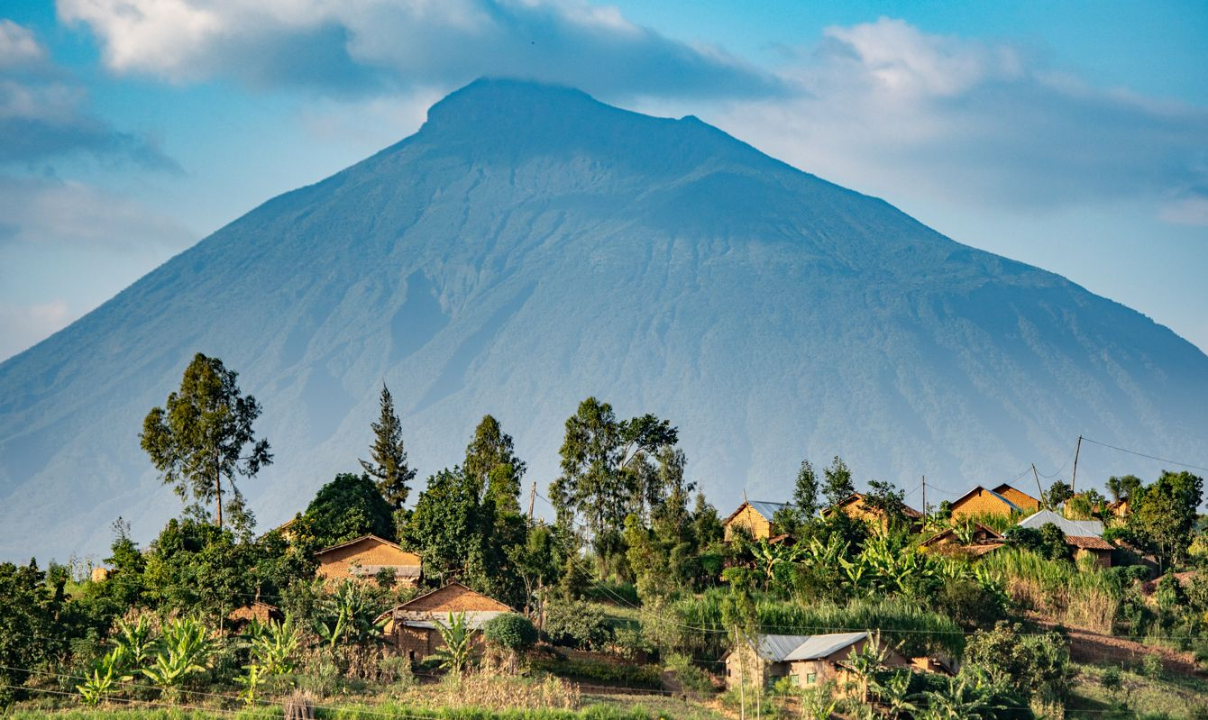 Houses in a small village are dwarfed by the looming presence of a volcanic mountain, Rwanda,