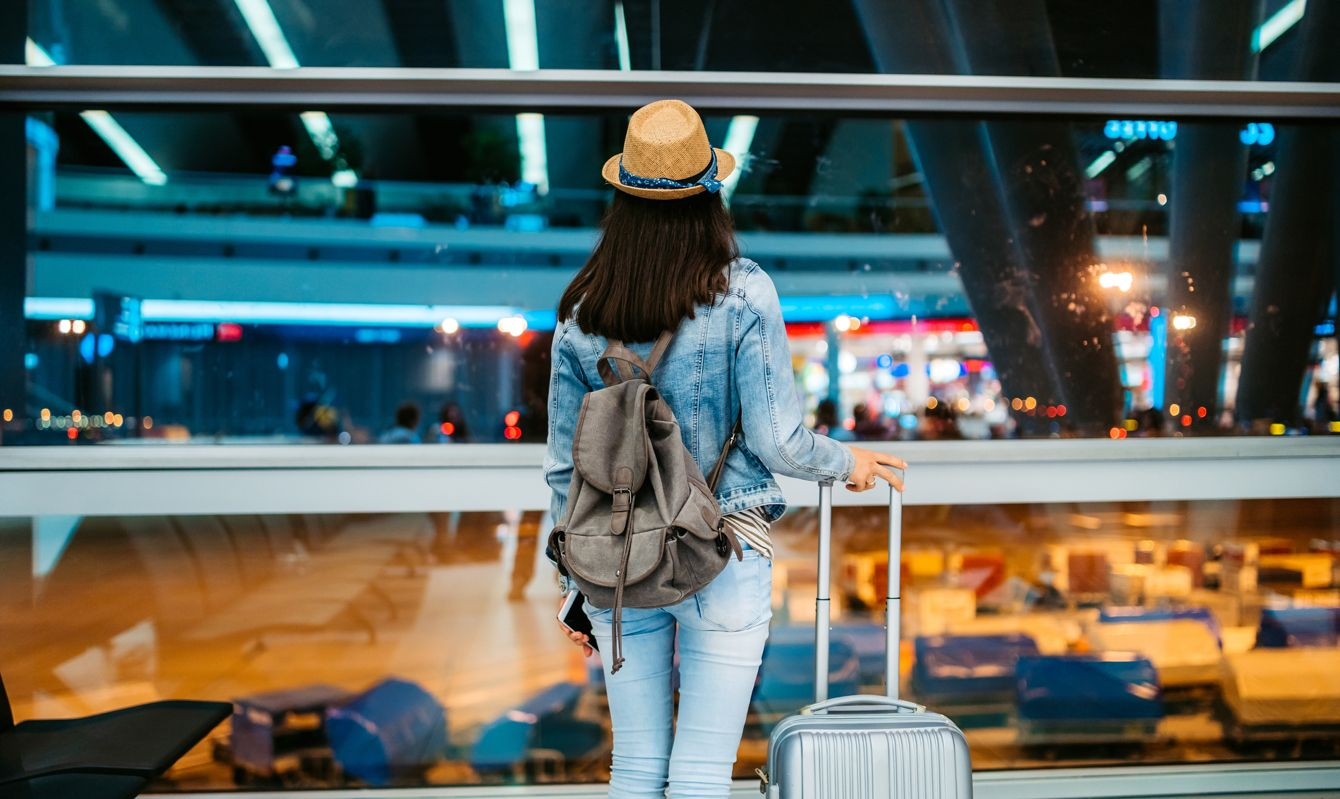 Young woman waiting for a flight, watching at runway from a departure board.