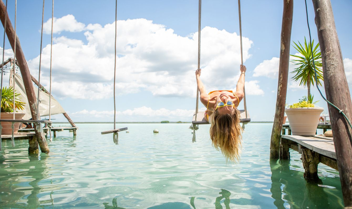 Woman playing on swing over the sea, Mexico, beautiful and idyllic landscape. People travel vacations concept.