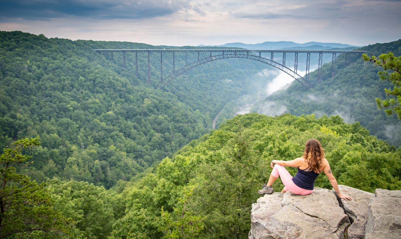 A woman perched on a rocky outcrop looks out over the New River Gorge Bridge in Wild West Virginia. A moody sky and foggy river below add drama.