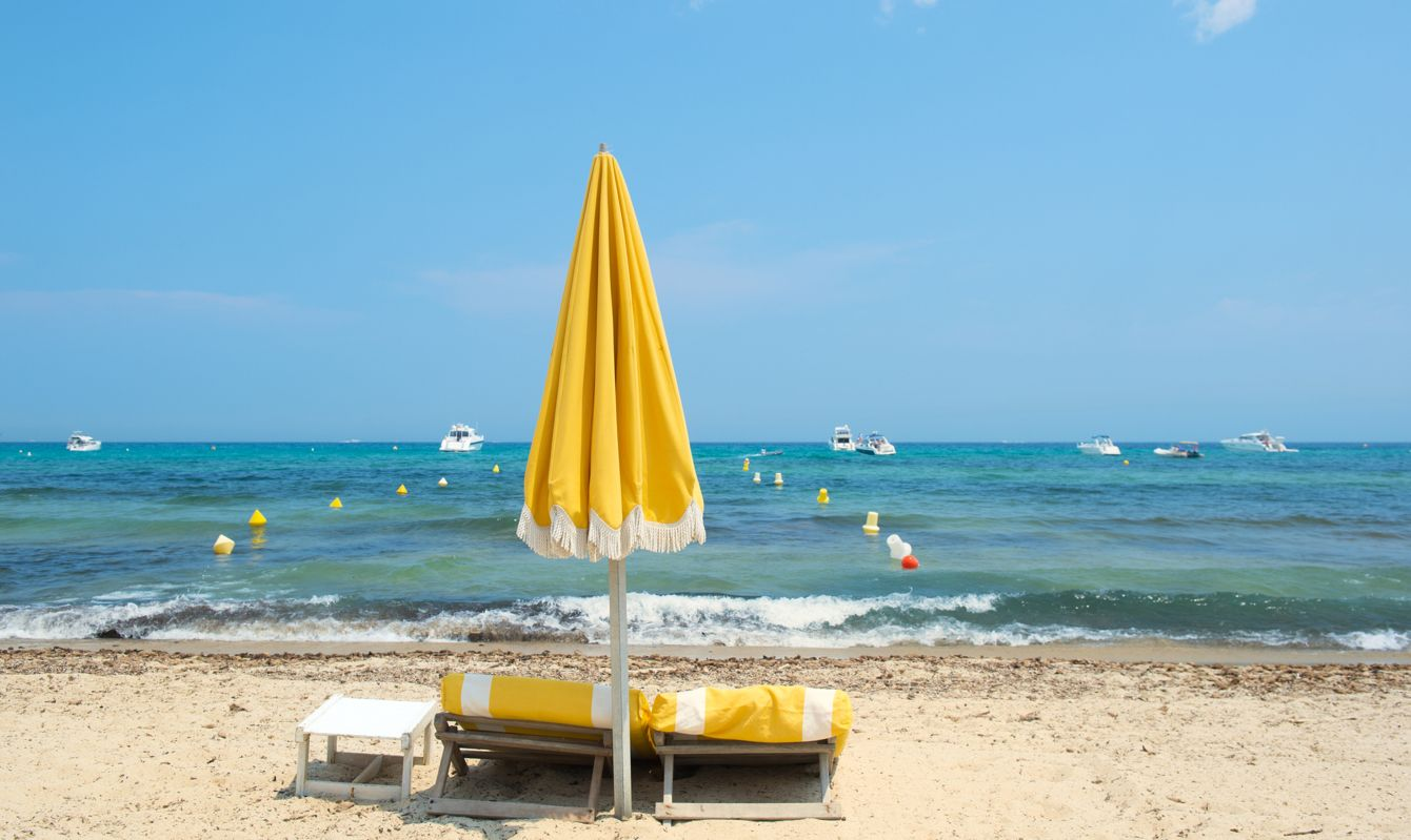 Beach with parasols, beds and luxury yachts