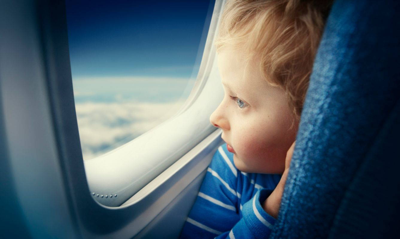 Curious young blonde boy watching sky from airplane window during flight