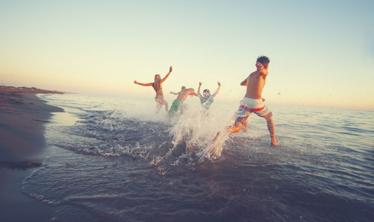Spring breakers running into the ocean