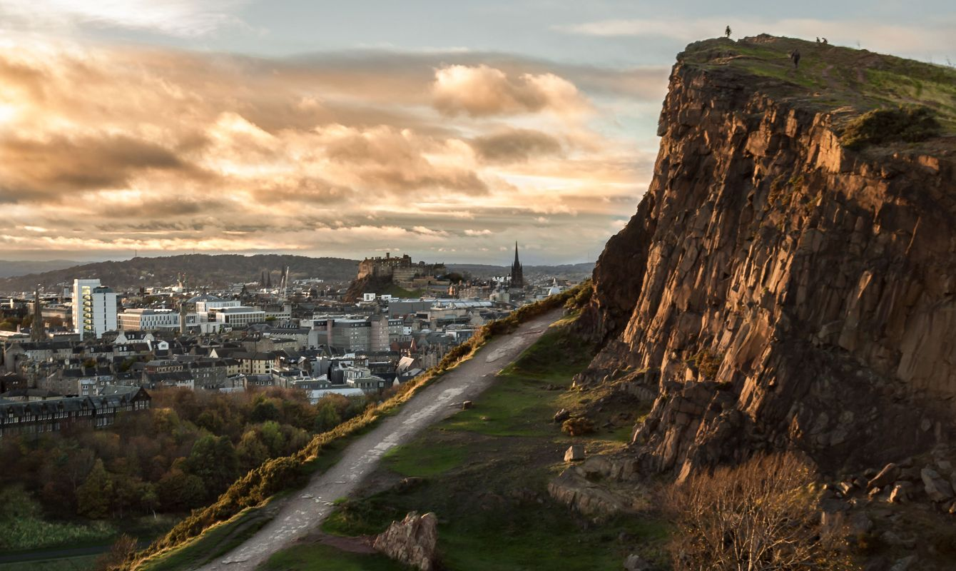 View of the Salisbury Crags at Holyrood Park, in Edinburgh, Scotland, with Edinburgh's Castle in the background, and evening light on the face of the cliffs and the clouds. Landscape. Cityscape. Travel.