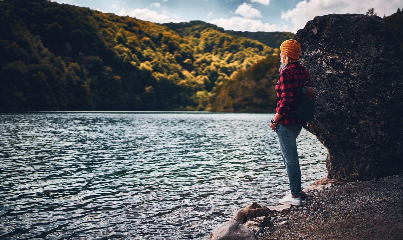 Woman tourist exploring Plitvice Lakes National Park at sunny autumn day. Croatia