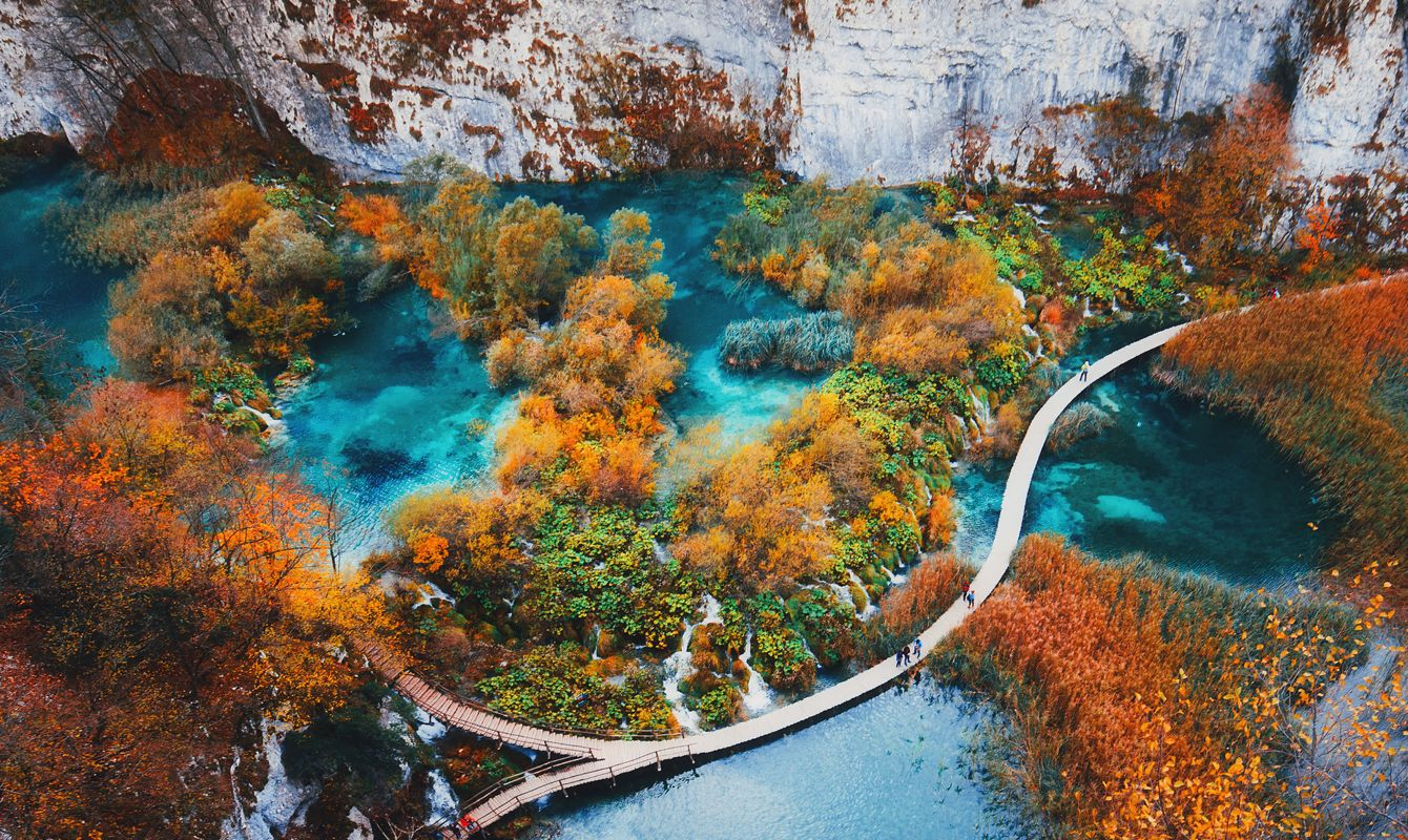 Beautiful view with wooden trekking path, autumn colors trees, lakes and waterfall landscape in Plitvice Lakes in Croatia