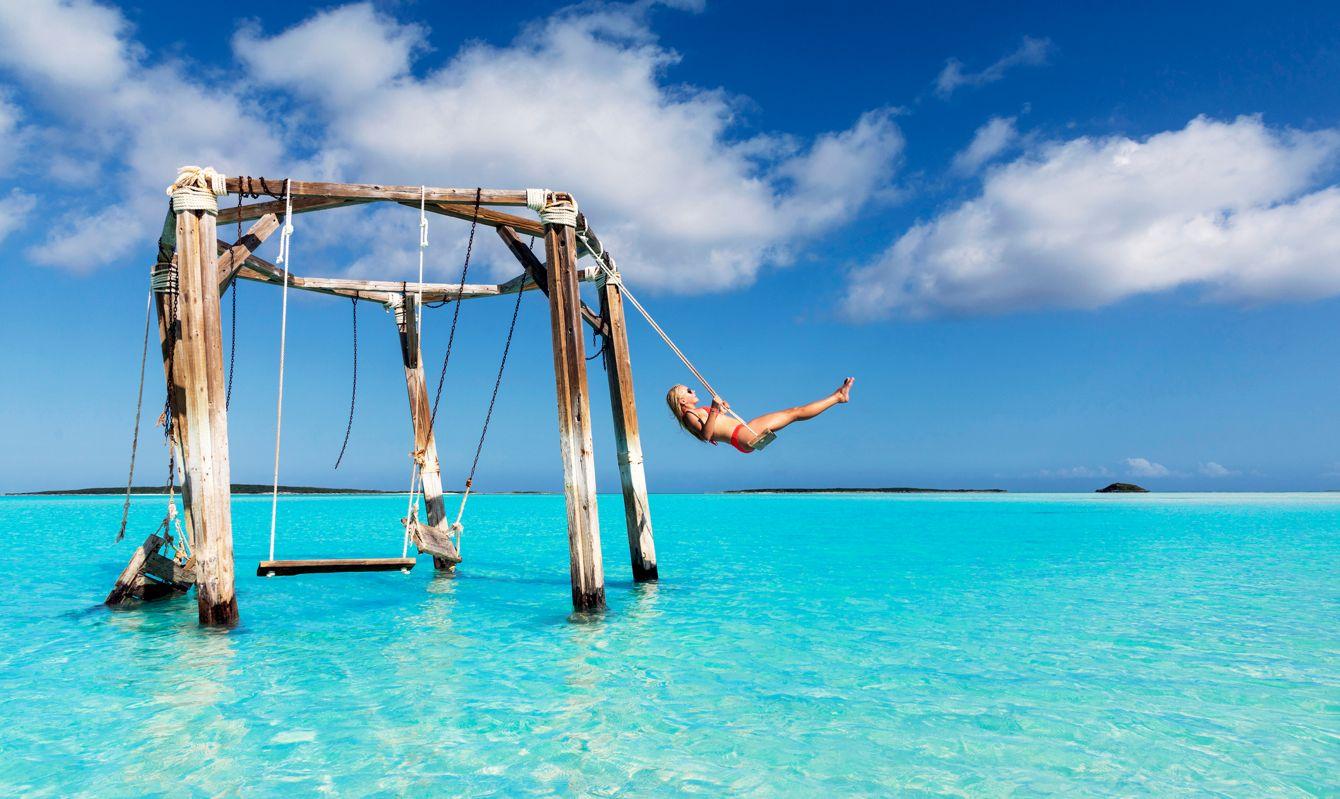 A girl swinging at Cocoplum Beach Exuma Bahamas.
