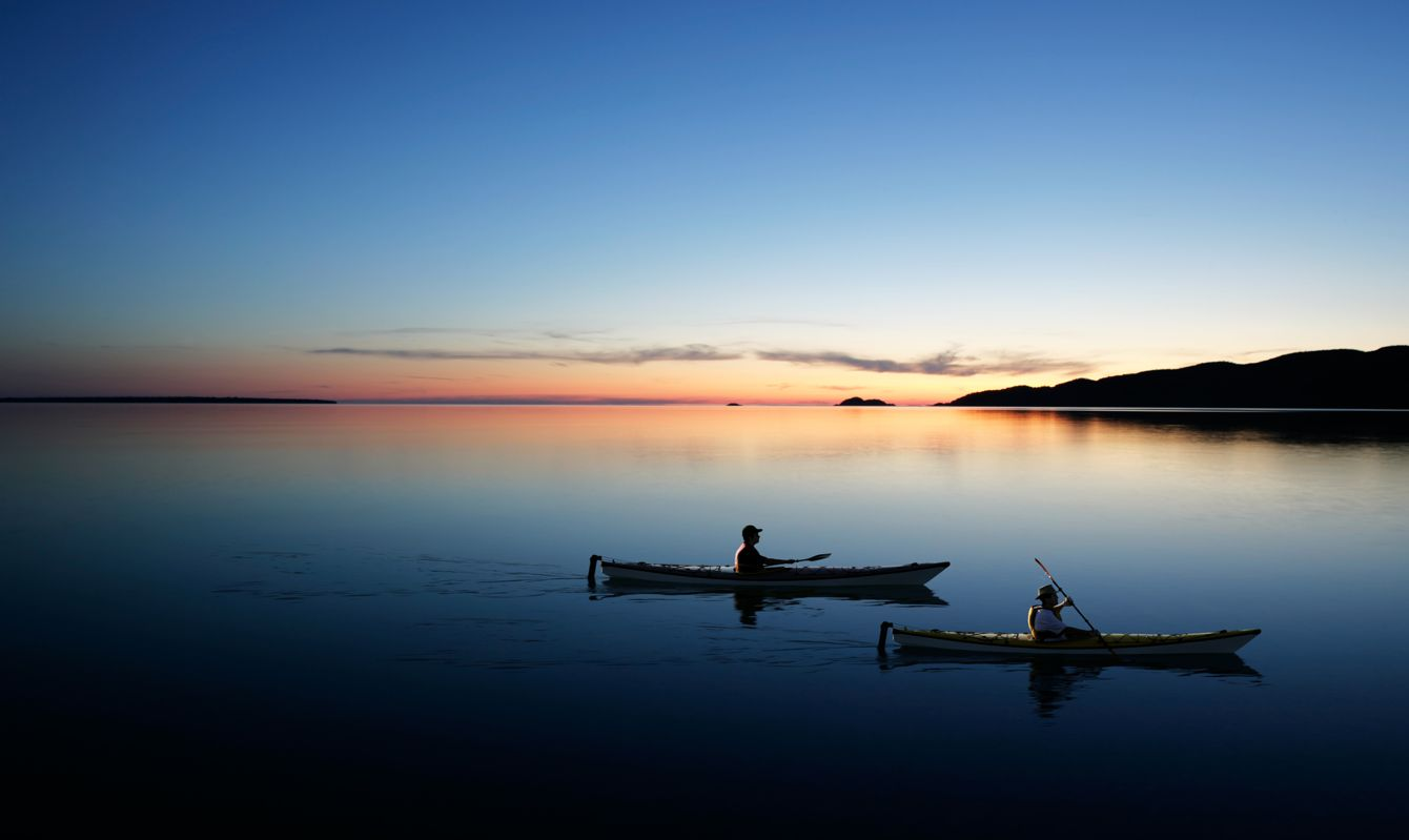 father and son kayaking on serene lake at twilight