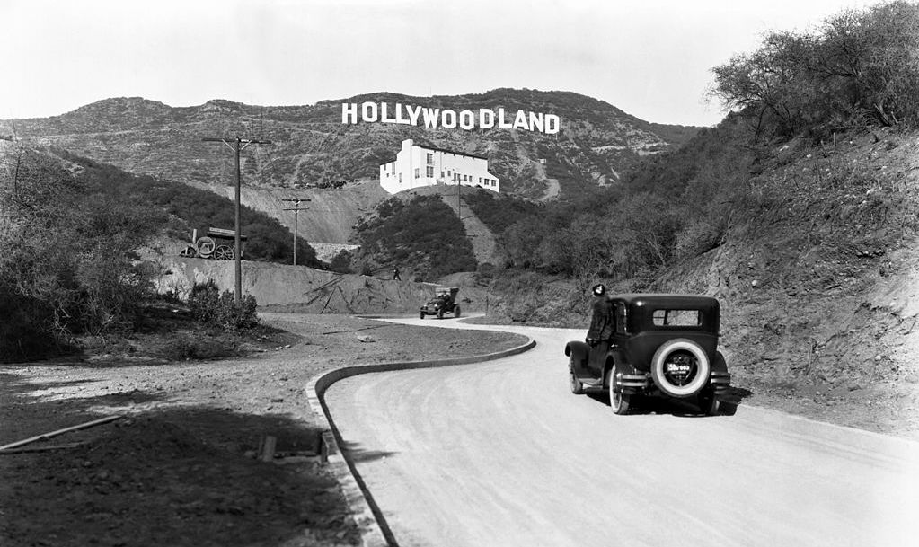 A sign advertises the opening of the Hollywoodland housing development in the hills on Mulholland Drive overlooking Los Angeles, Hollywood, Los Angeles, California, circa 1924. The white building below the sign is the Kanst Art Gallery, which opened on April 1, 1924.