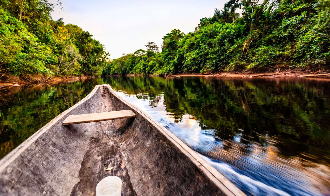 Sailing on Indigenous wooden canoe on a river in the Amazon state Venezuela