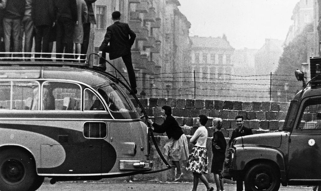 Sightseers climb onto a bus to look at the newly-built Berlin Wall.   (Photo by Keystone/Getty Images)