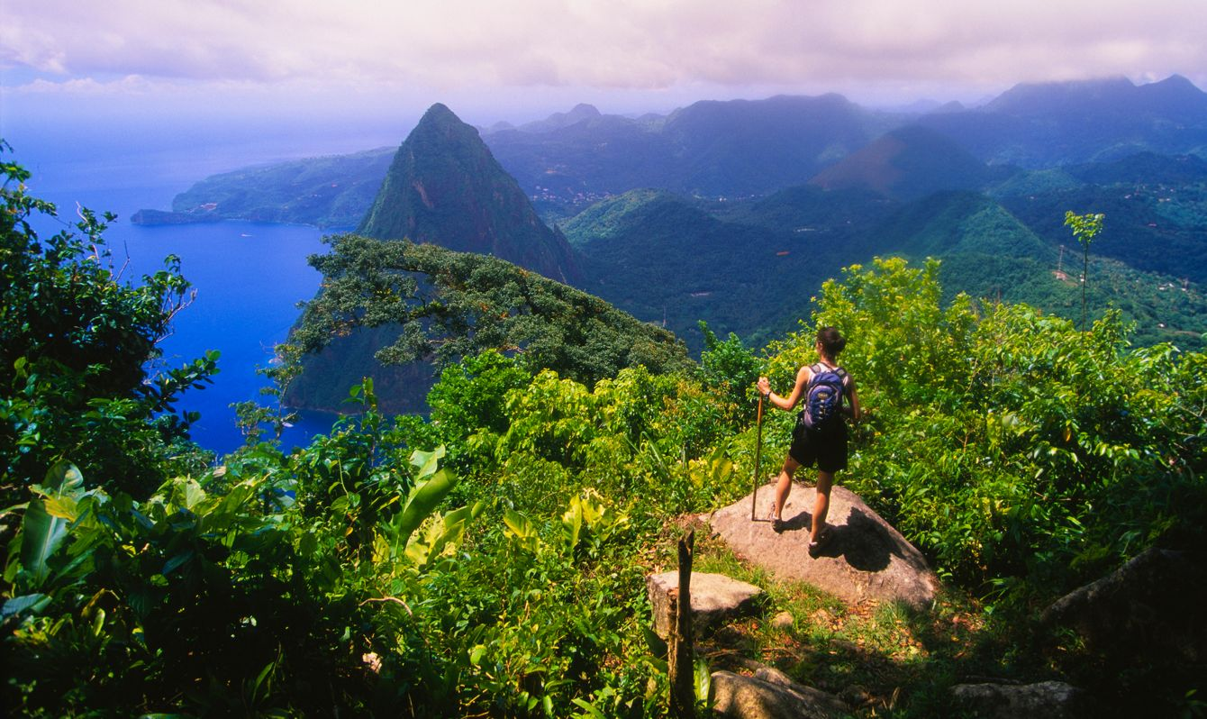 A hiker admires the view of Petit Piton from the top of Gros Piton. The two volcanic mountains make up The Pitons in St. Lucia, and are linked by the Piton Mitan ridge.